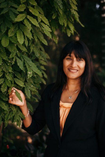 La Dra. Sarada Krishnan es una mujer de unos 40 años.  Tiene flequillo y cabello largo y sonríe junto a una planta de café.