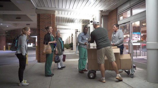 La gente se para frente a un hospital en una cabina que sirve tazas de café gratis a los trabajadores de la salud.