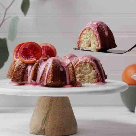 slice of bundt cake on a marble cake stand with pink blood orange icing