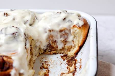side view of sourdough cinnamon roll with cream cheese icing