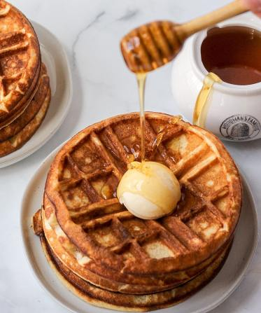 Waffles with big pat of butter and honey being drizzled on top