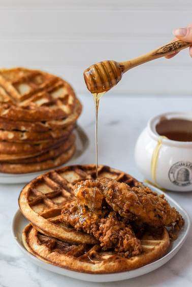 Sourdough waffles with fried chicken on top and honey being drizzled