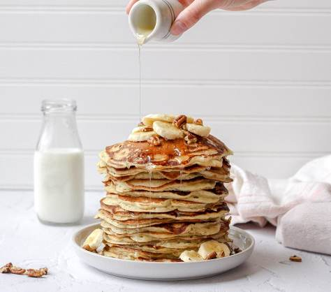 tall stack of sourdough pancakes with sliced banana, pecans, and honey