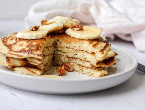 sourdough pancakes with a slice cut out topped with sliced banana and pecans
