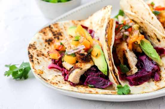 close up of grilled chicken tacos with mango salsa and cabbage slaw