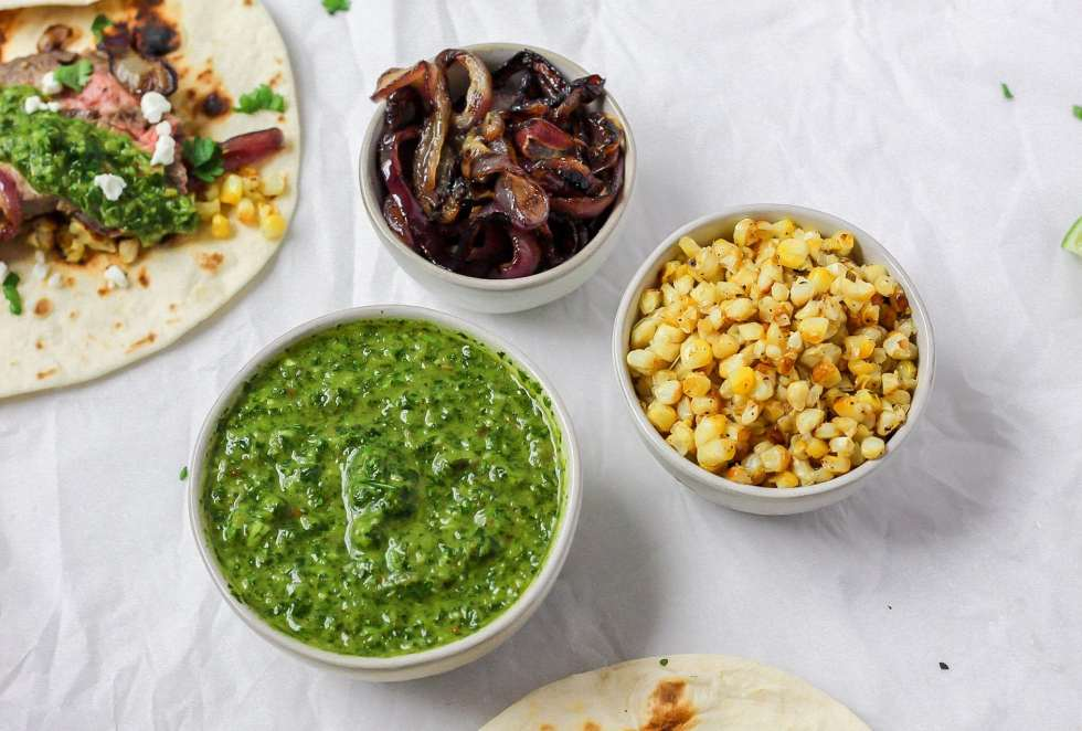 bowls of chimichurri, grilled corn, and grilled onions