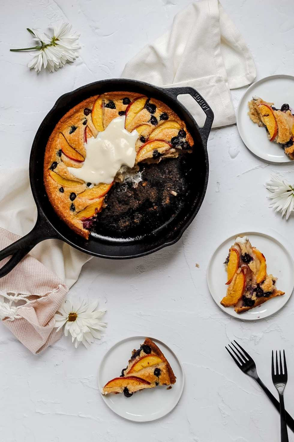 peach blueberry cobbler with whipped cream and pieces cut out