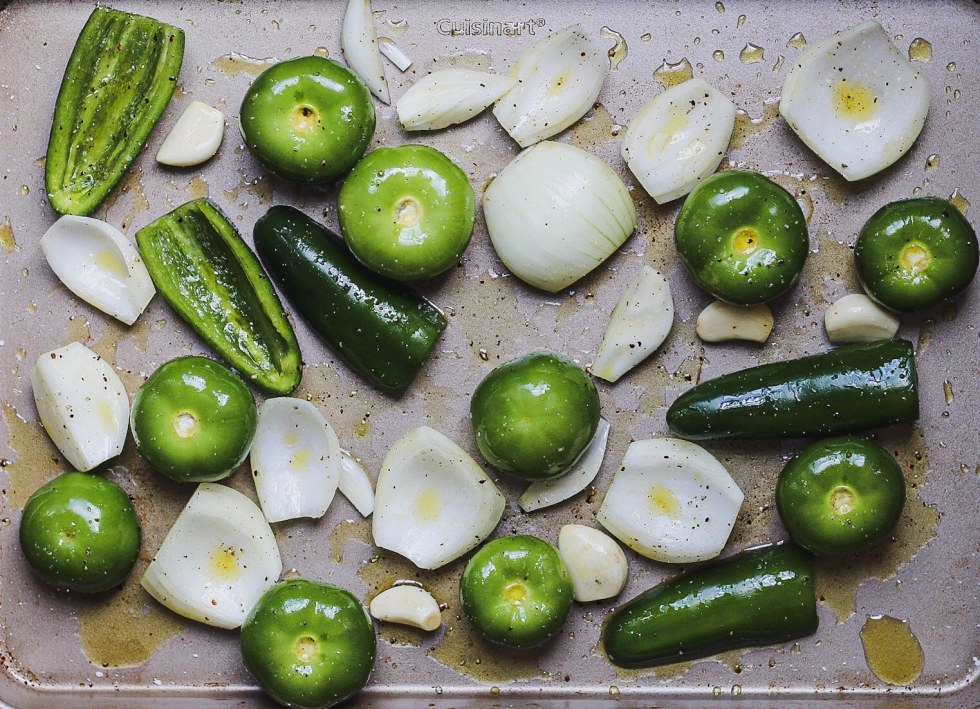 fresh tomatillos, jalapenos, onion, and garlic on baking sheet