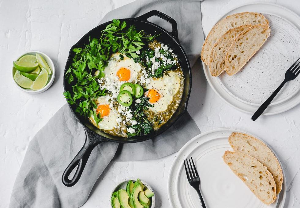 green tomatillo shakshuka with eggs and crusty sourdough bread
