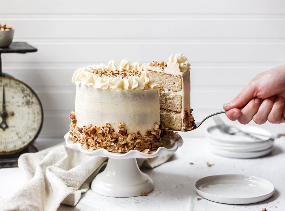brown butter hazelnut layer cake with slice being pulled out