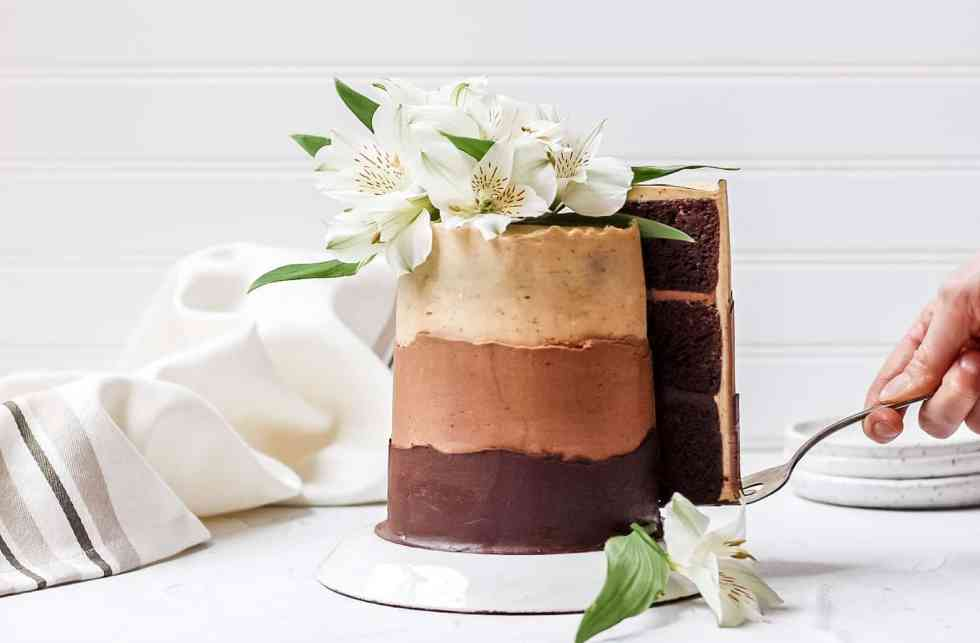 chocolate espresso ombre layer cake topped with fresh flowers with a slice being pulled out