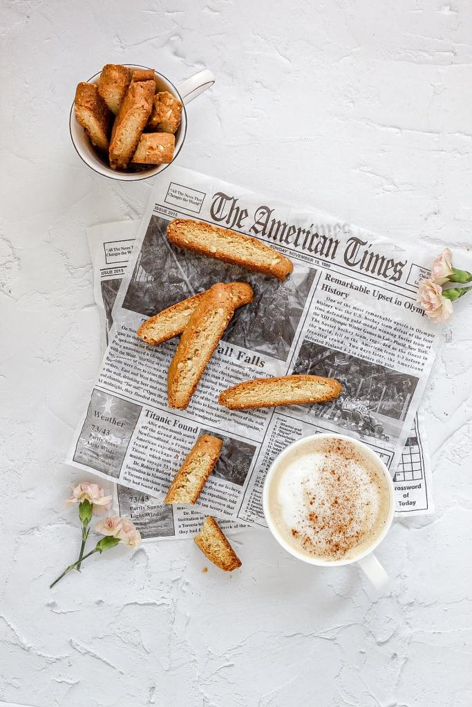 brown butter almond biscotti with newspaper and a latte