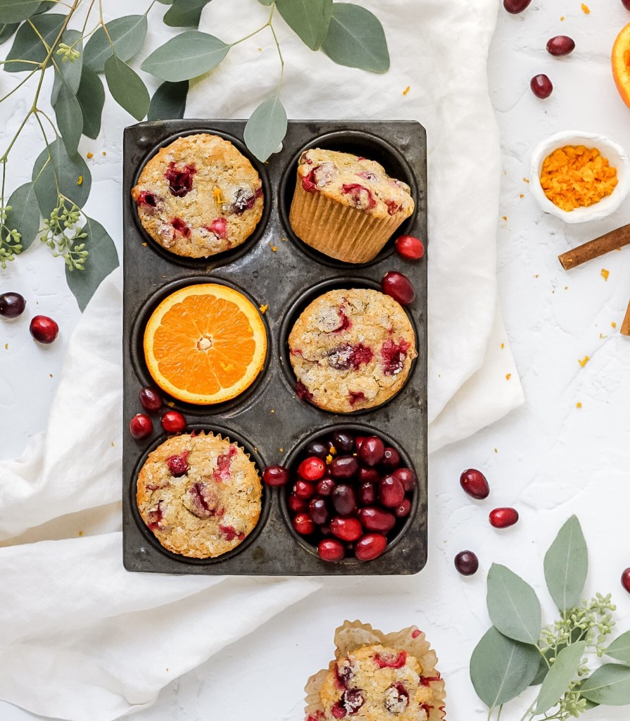 cranberry orange muffins in muffin rack with orange and cranberries