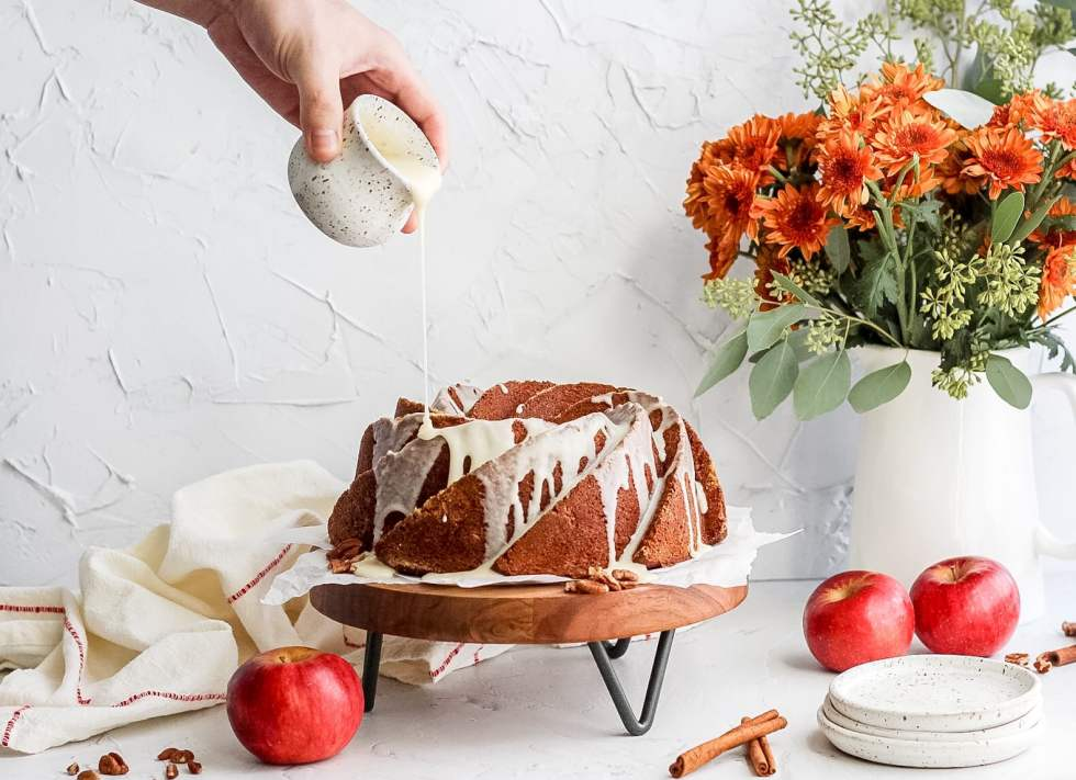 brown butter apple cider bundt cake with glaze being poured on top