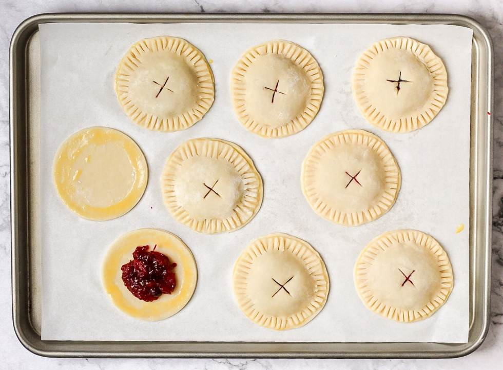 cranberry hand pies before baking. one hand pie open showing how to assemble