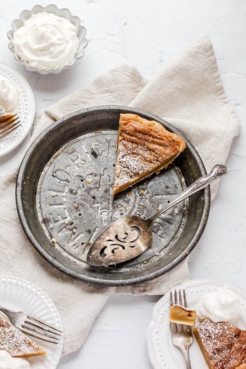 brown butter bourbon chess pie with homemade whipped cream and slices cut out