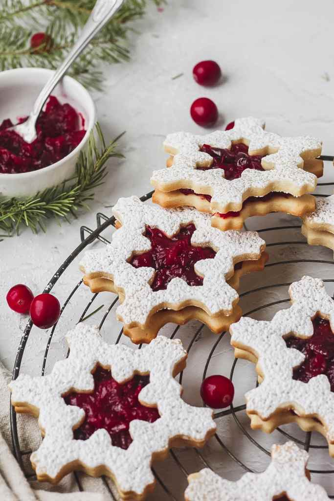 close up of cranberry linzer cookies shaped like snowflakes