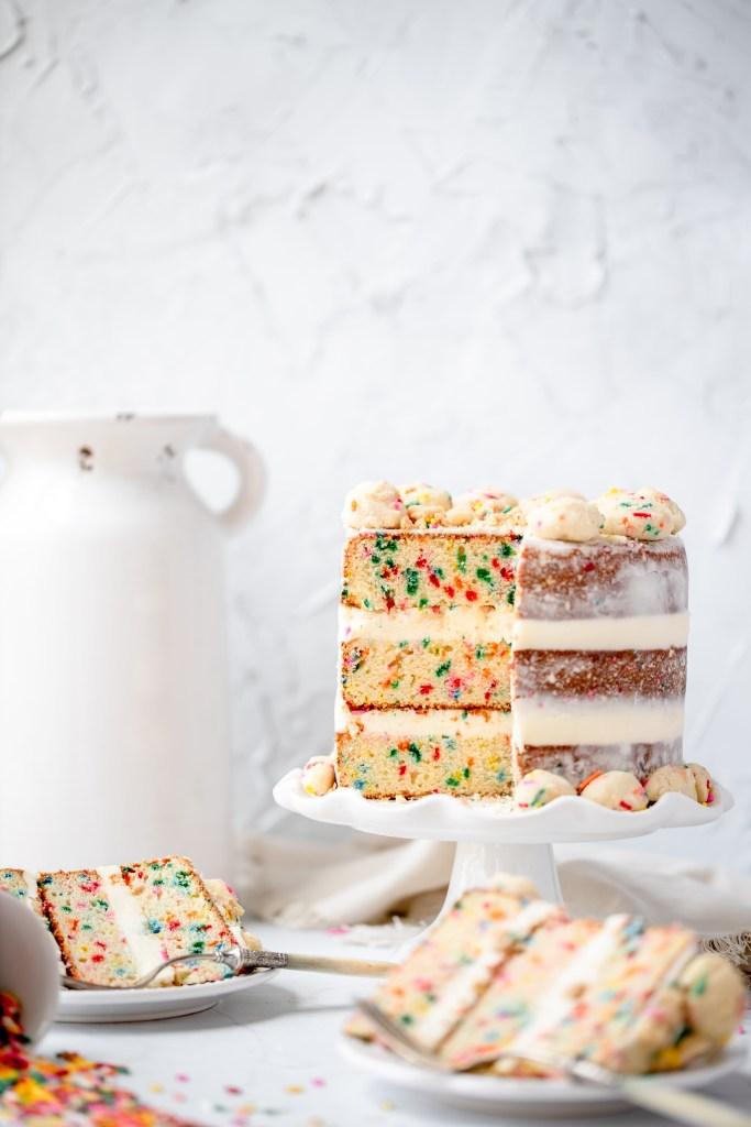 funfetti birthday cake with slice missing. milk bar copycat cake