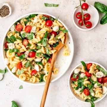 caprese pasta salad in large bowls
