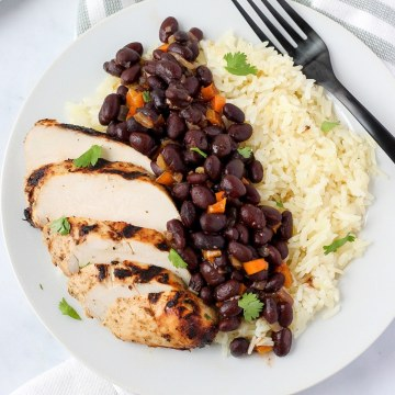close up shot of beans and rice with mojo chicken