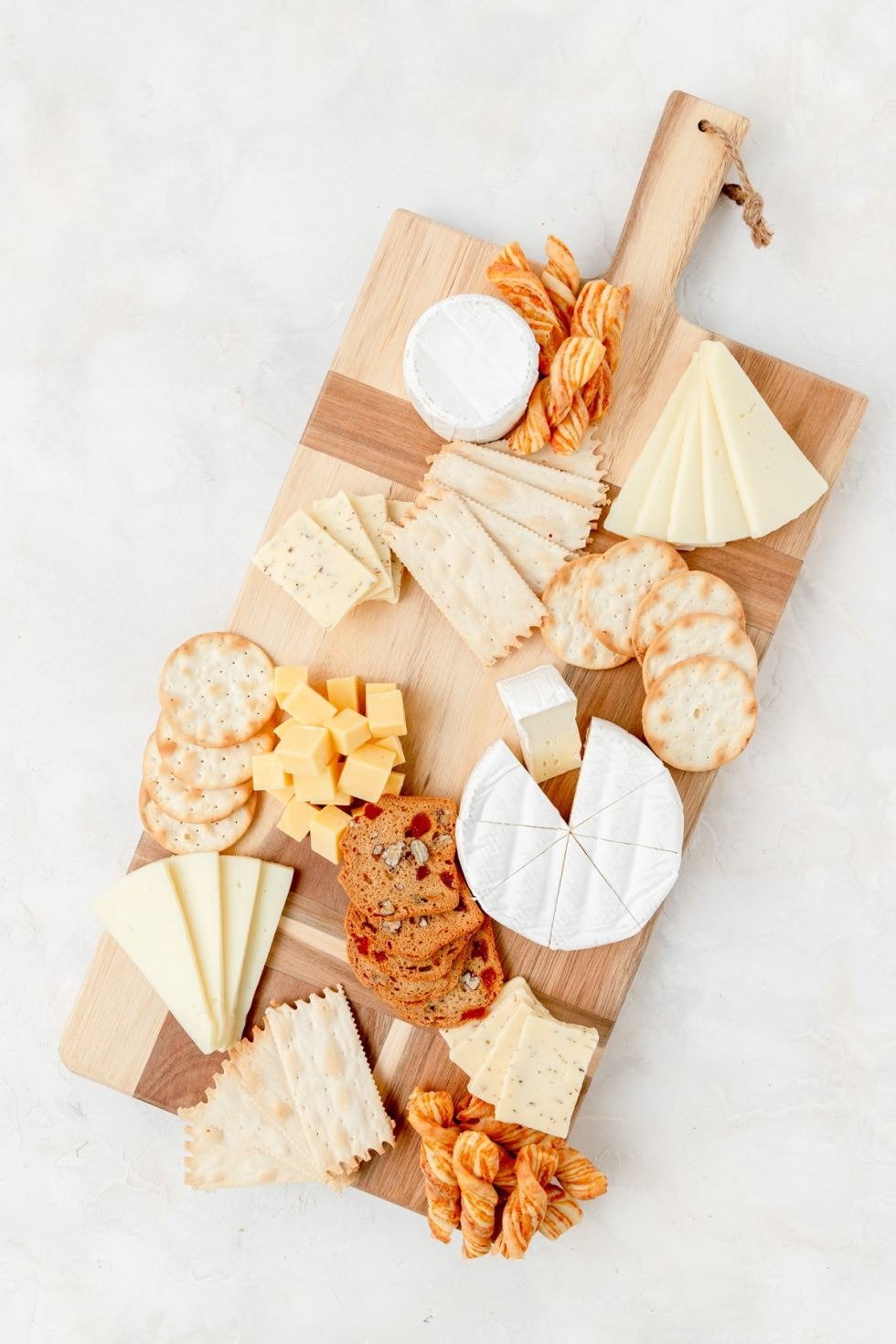 adding crackers to the board with cheese