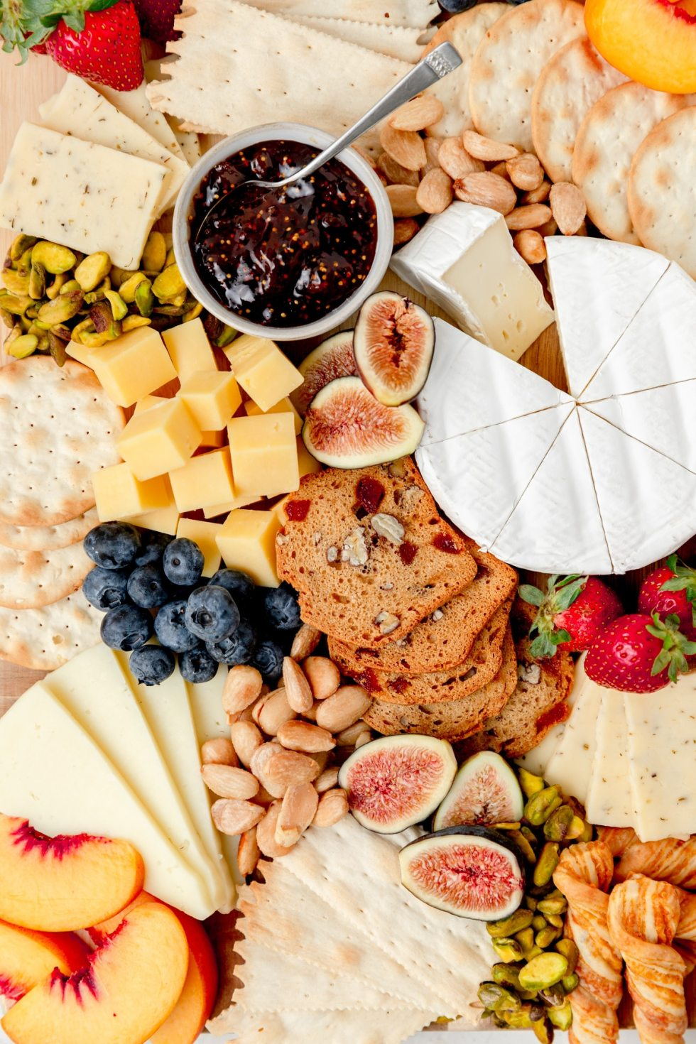 close up shot of fruit, cheese, and crackers