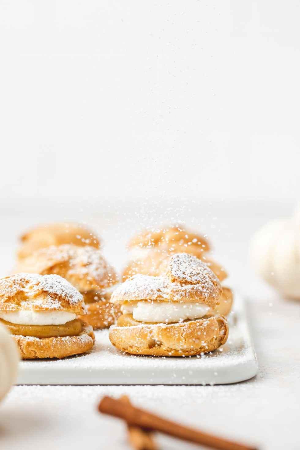 pumpkin cream puffs with powdered sugar on top