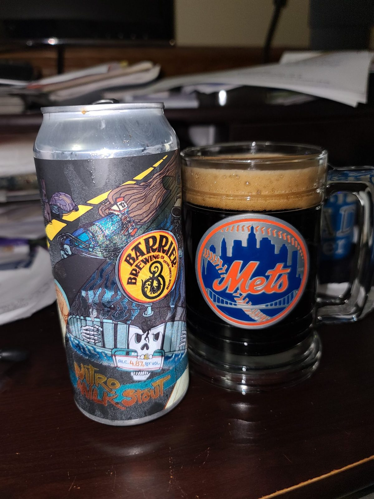 Beatiful fluffy tan head of foam in a Mets clear mug with ball logo on front, next to the Barrier can featured can art of the hood of a car
