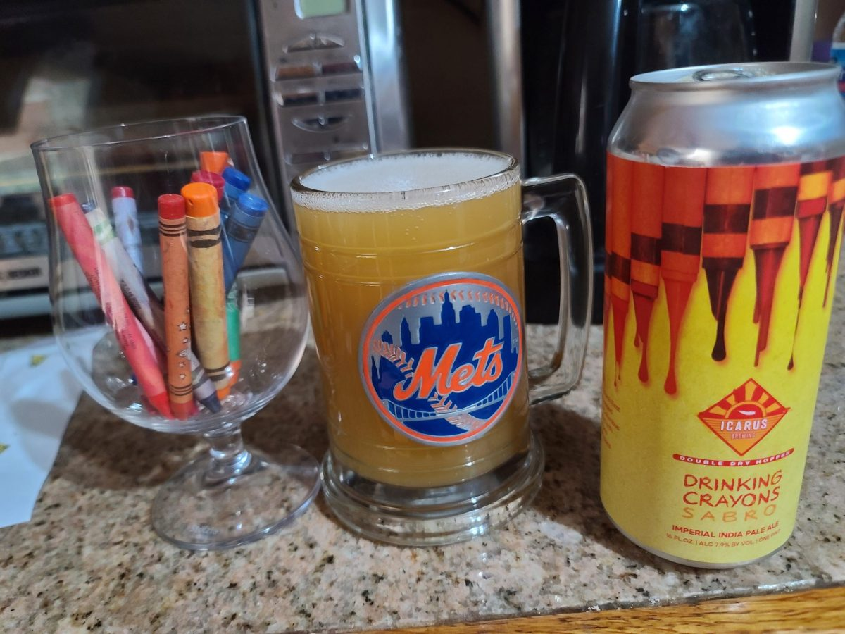 A can of Icarus Drinking Crayons next to a mug with the Mets logo holding the beer, yellow and hazy, next to a tulip glass with a handful of actual crayons in it to be funny