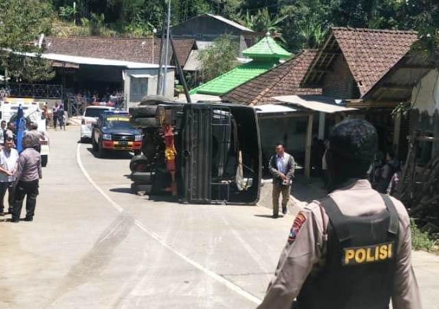 TERGULING: Truk Brimob pengamanan Presiden Jokowi terguling di Desa Nogosari, Kecamatan Pacet, Kabupaten Mojokerto, Kamis (6/9). | Foto: IST