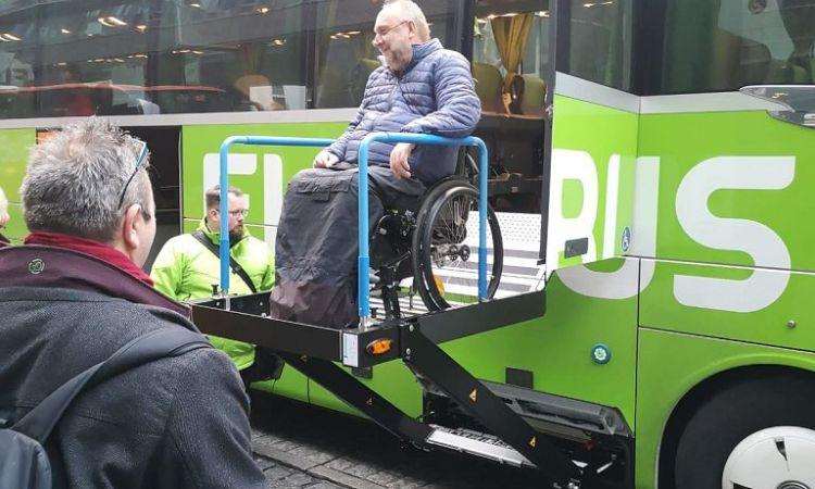 Rollstuhlfahrer auf dem Lift eines Fernbusses