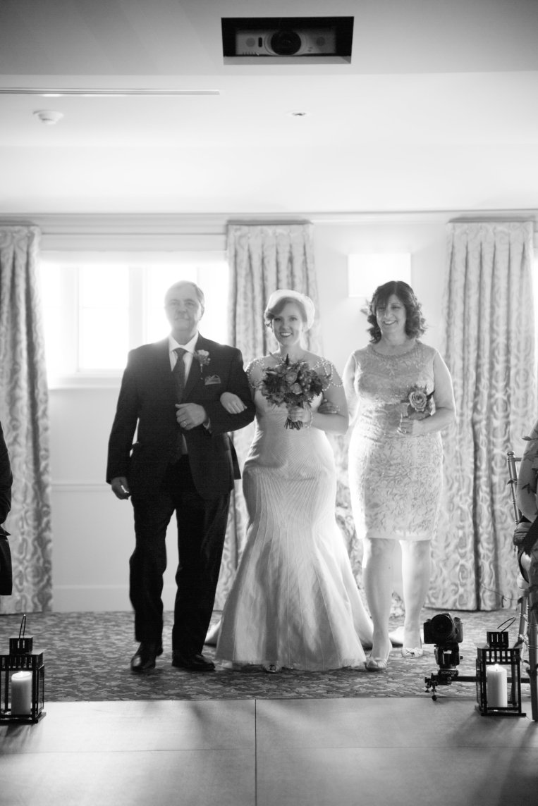 Bride and Groom with Mother and father Walking Down the Aisle