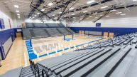 Gymnasium with basketball court and bleacher seating
