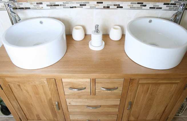 Close-Up View of Two White Ceramic Bowls on Large Oak Vanity Unit
