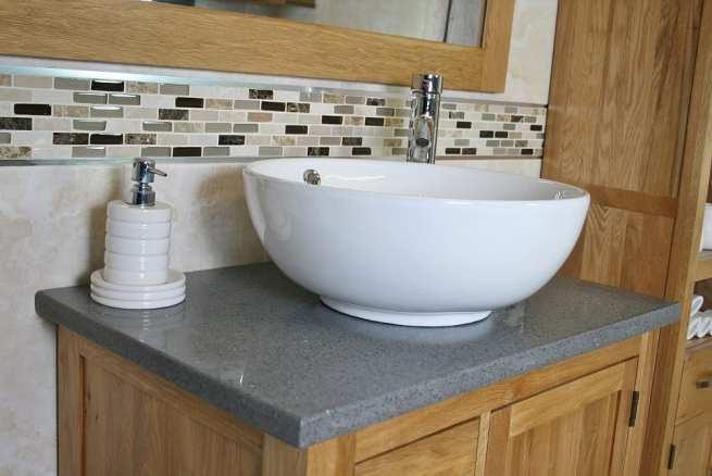 Side Closeup of Round Curved White Ceramic Basin on Grey Quartz Top Vanity Unit