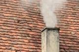 Alter rauchender Schornstein auf Hausdach