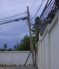 Strommast wird von vielen Stromkabel verbogen und kippt