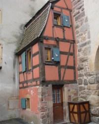Hälfte eines Fachwerkhauses das an eine Mauer grenzt