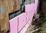 Rosa Perimeterdämmung vor Ziegelmauerwerk