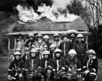 Familienfoto der Berufsfeuerwehr vor brennendem Haus
