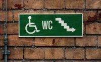 Hinweisschild für Rollstuhlfahrer für Toilette an unteren Ende einer Treppe