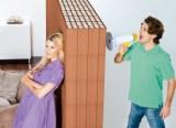 Mann mit Megaphon schreit durch eine dicke Hochlochziegelwand eine Frau an