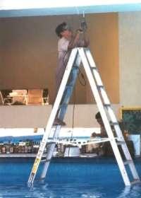 Mann steht in Schwimmbecken auf Leiter und bohrt mit Bohrmaschine