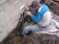 Mann steht in Pfütze und schraubt an Stromverteiler