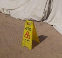 Schild mit Wet Floor vor einer Baustelle im Sand