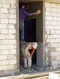 Bauarbeiter stützt Gerüst auf seinen Rücken