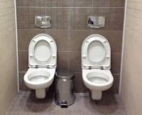 Zwei Toiletten Schüsseln nebeneinander ohne Trennwand