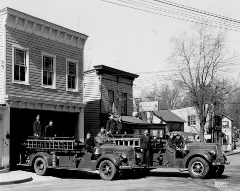PHOTO SHOWS THE 1938 MACK (LEFT) AND THE 1940 MACK (RIGHT) IN FRONT OF THE MAIN STREET STATION IN 1941