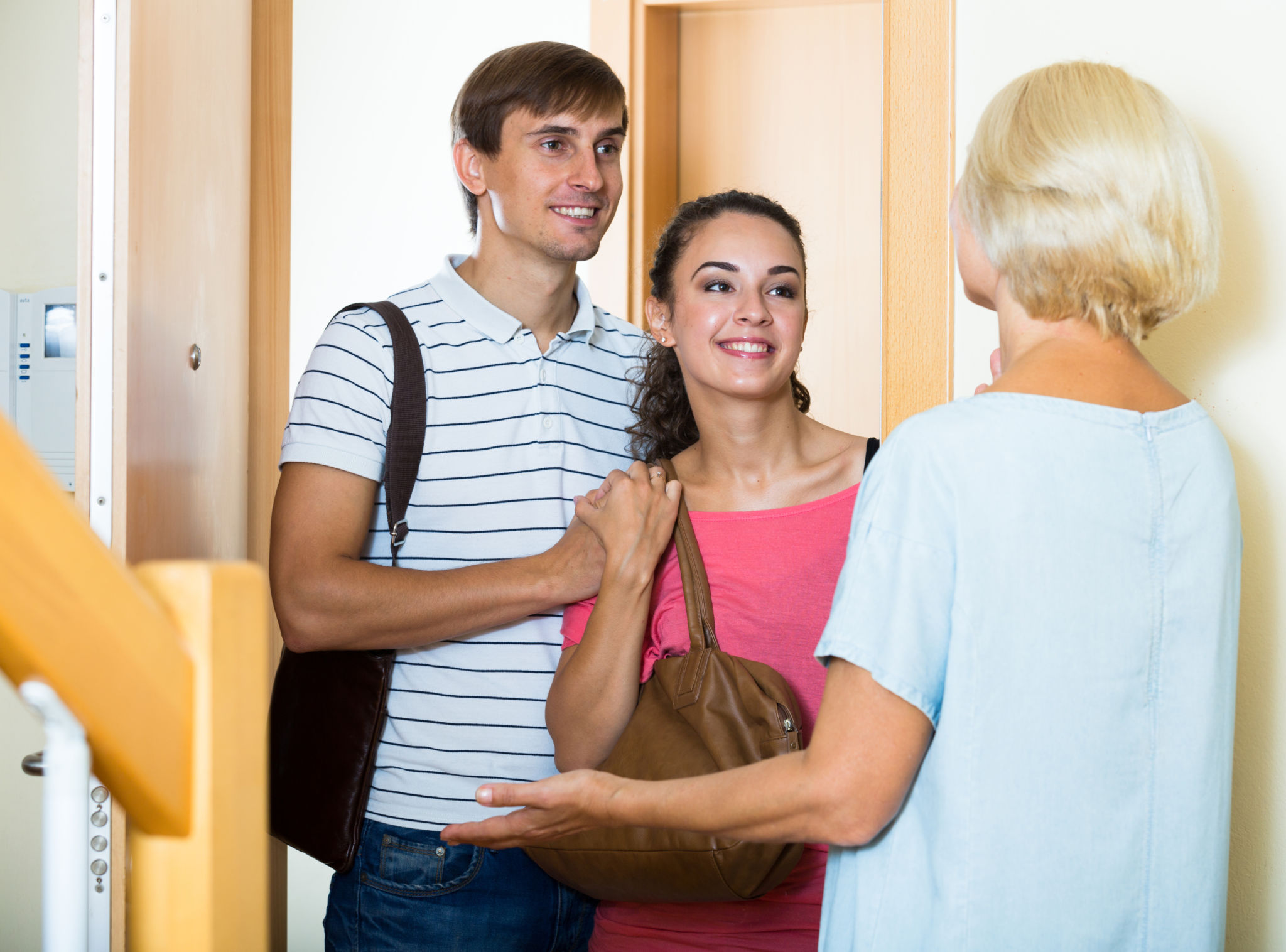 girlfriend meeting the parents for the first time, standing in doorway with boyfriend and his mom