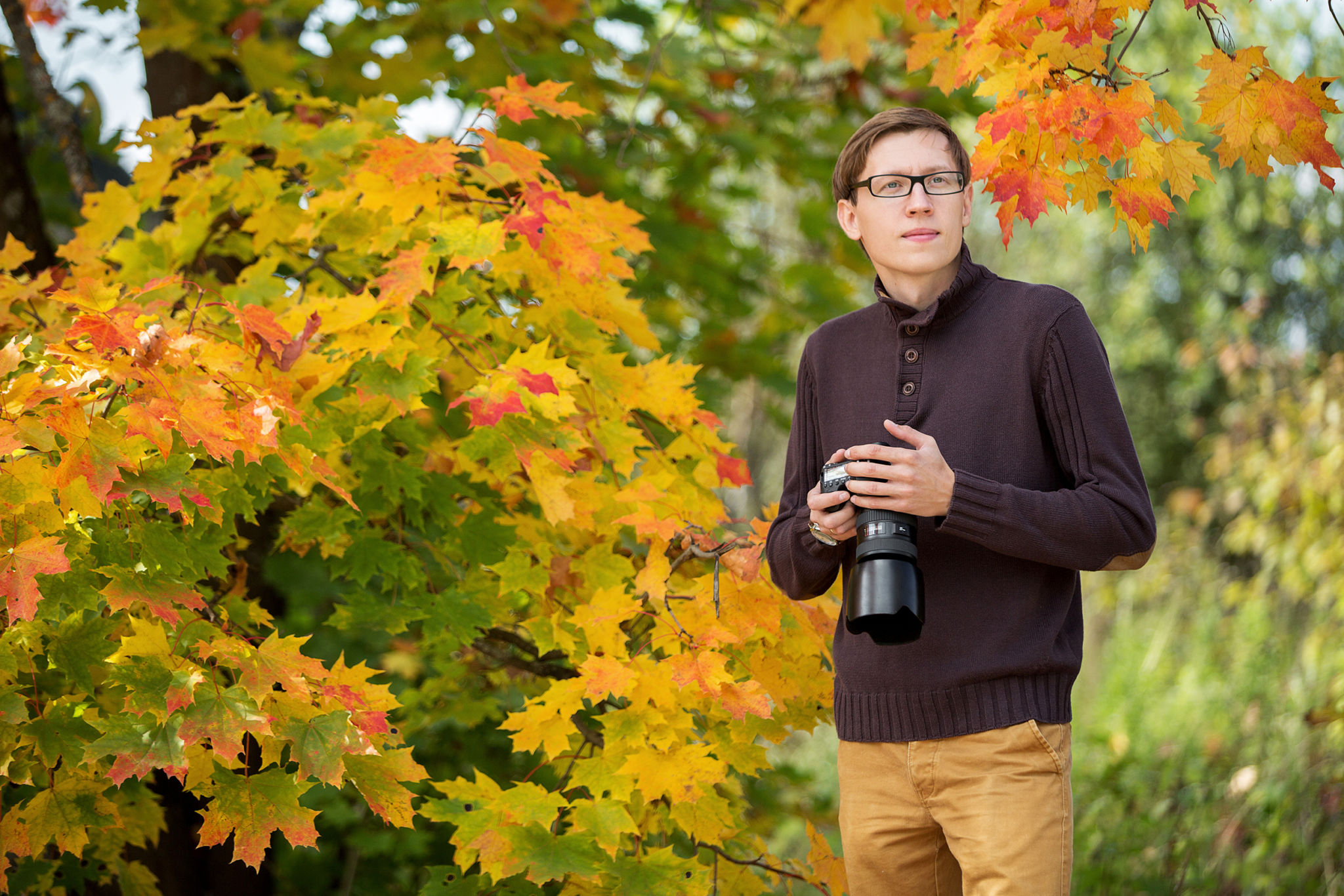 Man in autumn, holding a camera